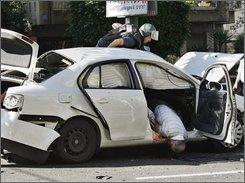 "An Israeli police officer from the bomb unit examines a car as the body of man hangs out of the passenger side door after an explosion in Tel Aviv, Monday Nov. 17,  2008. A huge car explosion in central Tel Aviv killed one of Israel's top mafia kingpin's on Monday, raising the likelihood of an all-out mob war in Israel's underworld. Israeli media identified the dead man as Yaakov Alperon_known informally as ""Don Alperon"" -- but police would not confirm the report. (AP Photo/Moti Milrod)"