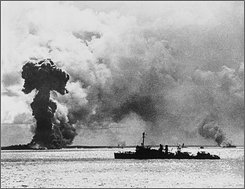"This file photo released by the Department of Defense on June 13, 1942 shows a U.S. destroyer patrolling the scene of destruction at Port Darwin, Australia after a Japanese air strike. The smoke column at left is from an exploding Australian ship said to have been loaded with bombs. The Feb. 19, 1942 attack is often referred to as the ""Pearl Harbor of Australia."" (AP Photo/File)"