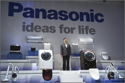 "Fumio Ohtsubo, president of Panasonic Corp., then Matsushita Electric Industrial Co., poses with a line of ""Hello Panasonic"" products in Tokyo Tuesday, Sept. 16, 2008 when he announces the Japanese electronics maker will scrap its Japanese brand name ""National"" and start a marketing blitz called ""Hello Panasonic"" in an ambitious drive to boost market share, starting Oct. 1. When Panasonic's acquisition of smaller Japanese rival Sanyo is completed, forming one of the world's biggest electronics makers, global consumers are likely in for little visible change in products lining store shelves -- at least for some time. (AP Photo/Katsumi Kasahara)"
