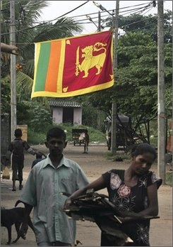People walk in their neighborhood as a Sri Lankan national flag is seen in the background in Colombo, Sri Lanka, Monday, Nov. 17, 2008. Sri Lankan government declared a week of celebrations starting Monday to pay tribute to the armed forces after the military announced it had dismantled the last rebel defense on the island's west coast and secured a land route to government-held Jaffna on Saturday. It was a key victory for the military, which has vowed to finally defeat the guerrillas by year's end. (AP Photo/Eranga Jayawardena)