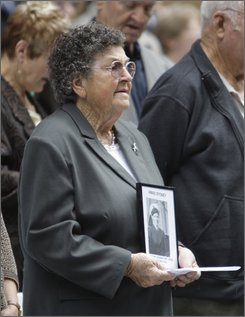 An unidentified woman holds a picture of Ordinary Seaman Theo Green during a memorial service in  Sydney, Australia, Wednesday, Nov. 19, 2008  for the sinking of  HMAS Sydney on Nov. 19 1941, after it battled with a German raider. (AP Photo/Rob Griffith)