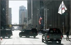 The motorcade of President-elect Barack Obama arrives at The Kluczynski Federal Building, the location of his Chicago transition office, Tuesday, Nov. 18, 2008. (AP Photo/Charles Dharapak)