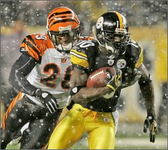 Pittsburgh Steelers receiver Santonio Holmes (10) runs after catching a pass from quarterback Ben Roethlisberger as Cincinnati Bengals cornerback Leon Hall (29) moves in to make the tackle during the second quarter of a  NFL football game  in Pittsburgh, Thursday, Nov. 20, 2008. (AP Photo/Gene J. Puskar)