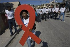 A demonstrator holds a red ribbon, the symbol of AIDS awareness, during a march marking World AIDS Day in Saint Marc, Haiti, Sunday, Nov. 30, 2008. Haiti, a nation of 9 million, remains the most affected by HIV in the Caribbean, itself the region with the highest infection rate outside Sub-Saharan Africa. (AP Photo/Ramon Espinosa)