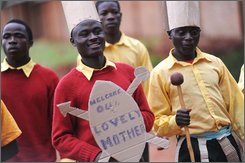"""Orphans of House of Hope Orphanage in Mchinji Tuesday March 31, 2009, dance with a sign saying """"Welcome our lovely mother"""" for the visit of US popstar Madonna. She adopted David Banda from this orphanage in Malawi. (AP Photo/Riccardo Gangale)"""