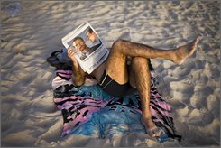 An Israeli man reads a newspaper as he rests on the beach in Tel Aviv, Israel, Thursday, March 5, 2009. In April 2009, Tel Aviv, the world's first purpose-built Jewish city, will mark its 100th anniversary with art shows, outdoor concerts and a all-night street party. (AP Photo/Oded Balilty)