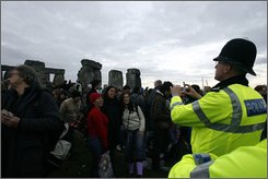 A police officer takes a photograph of revellers as people gather to celebrate the summer solstice at Stonehenge in west England, early Sunday, June 21, 2009.  The monument attracted some 35 thousand people to mark the longest day of the year when the sunrise was expected at 4:58 am under the cloudy sky. (AP Photo/Akira Suemori)