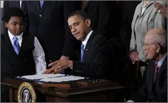 FILE - In this March 23, 2010 file photo, Marcelas Owens, 11, from Seattle, Wash., left, and Rep. John Dingell, D-Mich., right, look on as President Barack Obama signs the health care reform bill, in the East Room of the White House in Washington. Doubted and deeply in need of a comeback, President Barack Obama had a political dream week