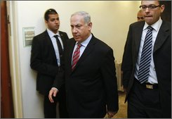 "Israel's Prime Minister Benjamin Netanyahu, center, arrives at the weekly cabinet meeting in Jerusalem, Sunday, March 28, 2010. Trying to tamp down tensions with the U.S. in his first comments since meeting President Barack Obama last week, Israeli Prime Minister Benjamin Netanyahu says Israel and the U.S. are ""allies and friends"" and can work out their differences. (AP Photo//Ronen Zvulun, Pool)"