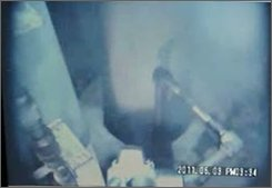 In this June 3, 2011 photo released by Tokyo Electric Power Co., workers try to install a pressure indicator inside the Unit 1 reactor at Fukushima Dai-ichi nuclear power plant in Okuma, Fukushima Prefecture, northern Japan. (AP Photo/Tokyo Electric Power Co.) EDITORIAL USE ONLY
