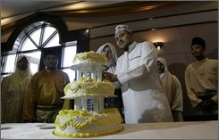 "In this picture taken June 4, 2011, newly wed couples cut a wedding cake as they attend a mass wedding ceremony in conjunction with the launch of the ""Obedient Wife Club"" in Kuala Lumpur, Malaysia. A Malaysian Muslim group has launched the ""Obedient Wives Club"" to teach women to be submissive and keep their spouses happy in the bedroom as a cure to social ills. (AP Photo)"