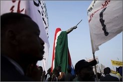 People gather around a statue of former Southern Sudanese leader John Garang, draped in the national flag of South Sudan, during independence celebrations in Juba, South Sudan, Saturday, July 9, 2011. South Sudan raised the flag of its new nation for the first time on Saturday, as thousands of South Sudanese citizens swarmed the capital of Juba to celebrate the country's birth. (AP Photo/David Azia)