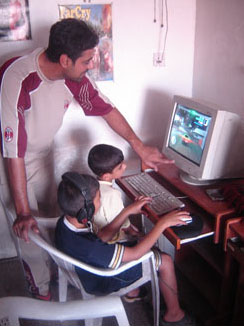 Video arcade owner Salah al-Faham (standing) adjusts a computer monitor for his customers, Ahmad Hussein (blue shirt) and his brother Thair Hussein at the al-Faham Brothers Arcade in east Baghdad June 21.