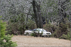 The automobile in which Gloria Shirk was in when she was swept off of FM 306 an into Rebecca Creek near Canyon Lake, Texas, during a rain storm Sunday, is shown lodged against a tree line March 12, 2007. Shirk's body was found Monday a quarter of a mile downstream from her car.