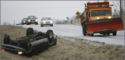 An Illinois Department of Transportation snow plow passes by the scene of a rollover wreck Thursday, Feb. 21, 2008, as it heads south on Illinois State Route 159, in Belleville, Ill. Nobody was injured in the wreck.