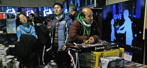 Helen Xu, left, John Xu, and Mario Ramos stand in the check-out line after waiting outside Best Buy since 8:00 p.m. the previous evening to shop at 5:00 a.m. on Black Friday in McLean, Va., on Friday, Nov. 23, 2007.