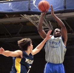 Kentucky's Darius Miller, right, takes a shot over University of Windsor's Evan Matthews during the first half of their exhibition game in Windsor, Ontario.