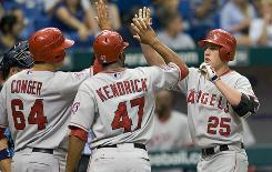 The Angels' Hank Conger, left, and Howie Kendrick, center, congratulate Peter Bourjos at the plate he hit a three-run home run during Anaheim's victory over Tampa Bay on Sunday.