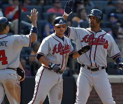 Derrek Lee, right, celbrates his seventh-inning grand slam with teammates, a blast that helped the Braves finish off a sweep of the Mets.