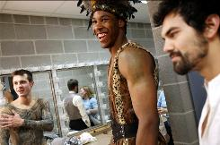 Delvon Roe, center, jokes with cast members Philip Krull, right, and Tom Brennan, left, while getting ready for a dress rehearsal of Shakespeare's As You Like It at Michigan State on Sunday. Roe is also a force for Michigan State's second-ranked men's basketball team.