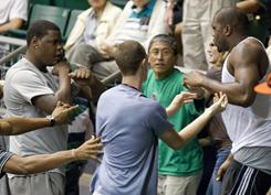 Mississippi State's Renardo Sidney, far left, and Elgin Bailey, far right, fight in the stands before the start of the Utah-Hawaii basketball game at the Diamond Head Classic Thursday.