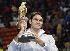 Roger Federer holds up the trophy after beating Nikolay Davydenko to win the Qatar Open.