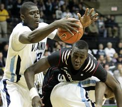 Villanova's Mouphtaou Yarou, left, grabs a loose ball from Cincinnati's Yancy Gates during the first half in Villanova, Pa. The Wildcats handed the Bearcats their first loss of the season.
