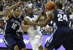 Connecticut's Kemba Walker loses control of the ball as he drives on Villanova's Corey Fisher, left, and Corey Stokes during their matchup in Storrs, Conn. Walker later hit a runner with 2.5 seconds left that gave the Huskies a 61-59 victory.
