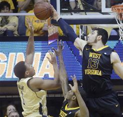 Notre Dame's Tyrone Nash has his shot blocked by West Virginia's Deniz Kilicli (13) as John Flowers looks on during the first half of the Mountaineers' upset victory in Morgantown, W.Va.