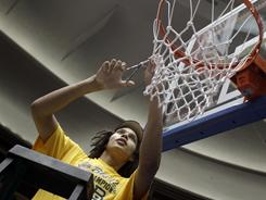 Baylor's Brittney Griner cuts does her part of the net following the Bears' 61-58 victory over Texas A&M in the Big 12 championship game.