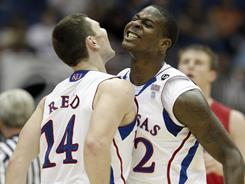 Kansas' Tyrel Reed (14) and Josh Selby celebrate during the Jayhawks' win over Richmond during the Southwest Regional semifinal in San Antonio.