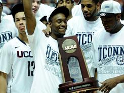 Kemba Walker and the Connecticut Huskies celebrate with the West Regional championship trophy after they beat Arizona in Anaheim, Calif., to earn a trip to the Final Four.