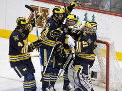 Michigan players celebrate after their semifinal defeat of North Dakota.