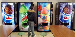 In this 2004 file photo, senior at Horlick High School in Racine, Wis., tries to decide what beverage to buy from the vending machines in the school cafeteria.
