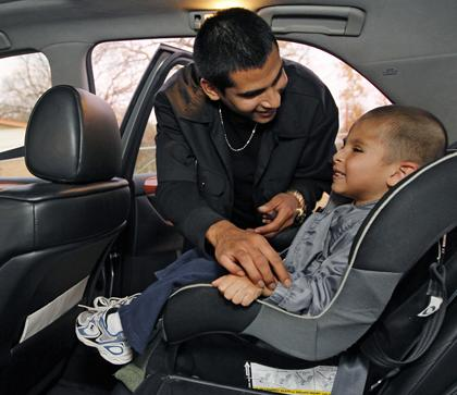 robert aleman 19 buckles his three year old son jonathan into the car seat as he picks him up at the day care in austin in december