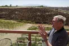 In this Sept. 17, 2010 photo, Ray Falkner, of the Falkner Winery, speaks in front of a hilltop, behind, that has been bought by the Calvary Chapel Bible Fellowship in Temecula, Calif. Some Temecula wineries are battling a local church with plans to expand, which they say could negatively affect their wine producing region.
