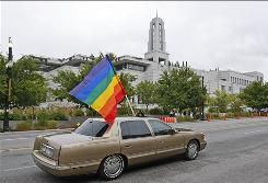 Protesters waving the rainblow flag, like those in this car shown last year driving by the  Mormon Conference, objected to recent remarks by a Mormon leader opposed to gay rights.