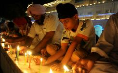 An Indian lawmaker asked President Obama to look into the airport security procedures that require searching the Sikh turbans worn by faithful observers of this religion. Here  Indian Sikh men and boys lit candles at the illuminated Golden Temple in Amritsa.Sikhs were disappointed that Obama did not include a visit to their shrine during his time in India.