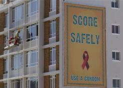 "A poster that promotes the use of Condoms in South Africa, seen on a building as workers clean windows, in Cape Town, South Africa, Monday, Nov. 22, 2010. Vatican officials insist it's nothing ""revolutionary,"" but to many other people Pope Benedict XVI's recent comments regarding condom use mark an important moment in the battle against AIDS and an effort by the pontiff to burnish his image and legacy."