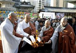 Buddhist monks in Seoul, South Korea burn the ancestral tablets of the victimized livestock during a memorial service for animals slaughtered to halt an outbreak of foot-and-mouth disease.