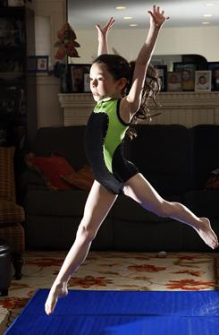 Orthodoz Jewish athlete Amalya Knapp, 7, shown doing her gymnastic warm-up at home in Teaneck, N.J., will not compete on the Sabbath.