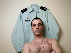 Army Sgt. Justin Griffith, showing his uniform and his A-for-atheist tattoo, is organizing other unbelievers in the military to seek the same privileges given religious groups in the military.