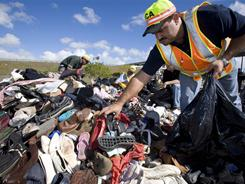 Javier Rolon, from a company that maintains roadways, bags shoes dumped on a Florida road that were donated to Soles4Souls, a shoe charity based in Nashville. The shoes weren't given to poor people; they were sold to middlemen instead.