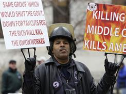 Walter Hudson, of Toledo, protests at the Ohio statehouse in March before passage of a bill stripping public employees of collective bargaining rights. Religious groups debate their role in this civic battleground
