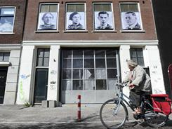 """Images of four Amsterdam Jews who died in the Holocaust are seen on a building where they lived during the war in Amsterdam, Netherlands, as part of a Holocaust memorial project labeling 21,662 """"Jewish Houses,"""""""