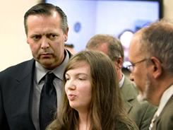 Timothy J. Wyland, left, 44, and Rebecca J. Wyland, center, 23, shown here at their arraignment in July, were set for trial today for choosing faith healing, not medicine, for their child's failing eyesight.