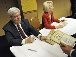Former House speaker and current Republican presidential hopeful Newt Gingrich and his wife, Callista, sign their book Rediscovering God in America during an appearance in Minneapolis in May.