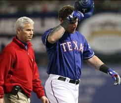 Josh Hamilton is accompanied off the field by a Rangers trainer after he was hit by a pitch on his left hand in Monday's spring training game. X-rays were negative. Hamilton has had a difficult time staying healthy throughout his career and he played in just 89 games last season.