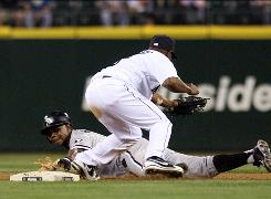 The White Sox's Juan Pierre, sliding under the tag of the Mariners' Chone Figgins, had 10 stolen bases and 17 runs scored in June. He leads the majors in steals with 35.