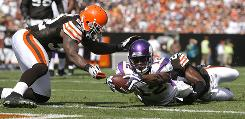 Minnesota Vikings rookie Percy Harvin dives for a touchdown as he is hit by Cleveland Browns defenders D'Qwell Jackson, left, and Brandon McDonald.